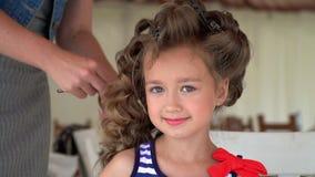 Haga a la niña un compensar un photoshoot La muchacha preciosa espera cuándo a su completo un peinado almacen de metraje de vídeo