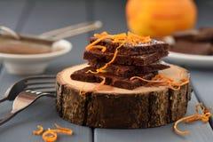 Haga las barras de chocolate a mano adornadas con las cáscaras de naranja en las losas de madera Foto de archivo