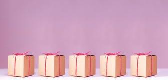 Haga las cajas de regalo a mano de la cartulina en el fondo rosado sólido holiday fotografía de archivo libre de regalías
