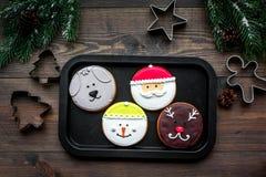 Haga las galletas del pan de jengibre por Año Nuevo en casa Panadería y cortadores en la opinión superior del fondo de madera Foto de archivo