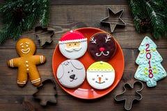 Haga las galletas del pan de jengibre por Año Nuevo en casa Panadería y cortadores en la opinión superior del fondo de madera Fotografía de archivo