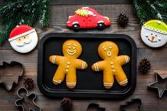 Haga las galletas del pan de jengibre por Año Nuevo en casa Panadería y cortadores en la opinión superior del fondo de madera Imágenes de archivo libres de regalías