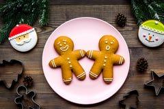 Haga las galletas del pan de jengibre por Año Nuevo en casa Panadería y cortadores en la opinión superior del fondo de madera Imagenes de archivo