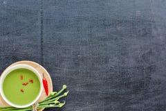 Haga puré la sopa y las verduras en una tabla negra Fotografía de archivo