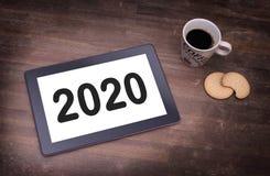 Haga tabletas el artilugio del ordenador del tacto en la tabla de madera - 2020 Foto de archivo libre de regalías