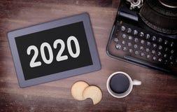 Haga tabletas el artilugio del ordenador del tacto en la tabla de madera - 2020 Fotos de archivo libres de regalías