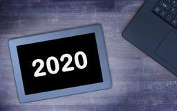 Haga tabletas el artilugio del ordenador del tacto en la tabla de madera - 2020 Imagen de archivo libre de regalías