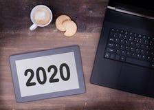 Haga tabletas el artilugio del ordenador del tacto en la tabla de madera - 2020 Foto de archivo