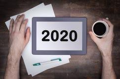 Haga tabletas el artilugio del ordenador del tacto en la tabla de madera - 2020 Imágenes de archivo libres de regalías