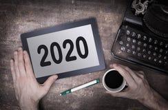 Haga tabletas el artilugio del ordenador del tacto en la tabla de madera - 2020 Imagenes de archivo