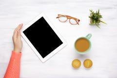 Haga tabletas el artilugio, la taza de café y dos molletes en una tabla de madera Imagen de archivo