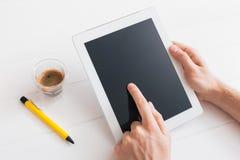 Haga tabletas el dispositivo sobre una tabla de madera blanca del espacio de trabajo Imagen de archivo