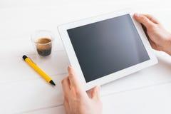 Haga tabletas el dispositivo sobre una tabla de madera blanca del espacio de trabajo Imagenes de archivo