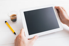 Haga tabletas el dispositivo sobre una tabla de madera blanca del espacio de trabajo Imágenes de archivo libres de regalías