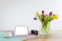 Haga tabletas la pantalla con el espacio de la copia y las flores en el escritorio de madera con el wh Fotos de archivo libres de regalías