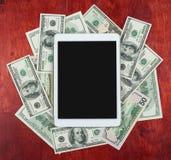 Haga tabletas la PC colocada en el centro del dólar del dinero y del fondo de madera, la pantalla en blanco oscura, el concepto d Foto de archivo libre de regalías