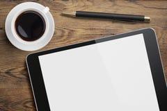 Haga tabletas la PC en el escritorio de la tabla con la taza y la pluma de café Imágenes de archivo libres de regalías