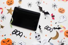 Haga tabletas la PC, las decoraciones del partido de Halloween y los caramelos Fotos de archivo libres de regalías