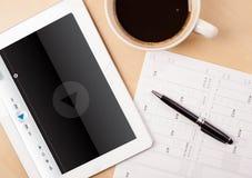 Haga tabletas la PC que muestra al reproductor multimedia en la pantalla con una taza de café encendido Foto de archivo libre de regalías
