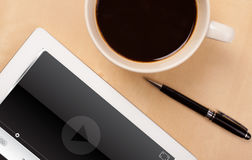 Haga tabletas la PC que muestra al reproductor multimedia en la pantalla con una taza de café encendido Foto de archivo