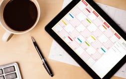 Haga tabletas la PC que muestra el calendario en la pantalla con una taza de café en una d Foto de archivo