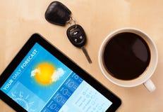 Haga tabletas la PC que muestra la previsión metereológica en la pantalla con una taza de coffe Fotografía de archivo
