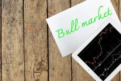 Haga tabletas y empapele con el mercado alcista del texto en la tabla de madera Foto de archivo libre de regalías