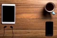 Haga tabletas y llame por teléfono con café en la madera con los auriculares Imagen de archivo libre de regalías