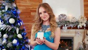 Haga un deseo, sople hacia fuera la vela, las miradas de la muchacha en una vela ardiente en el fondo del árbol de navidad y la c metrajes