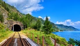 Haga un túnel el ferrocarril cerca del lago Baikal y el puente en primero plano Foto de archivo