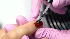Haga una manicura, aplicando esmalte de u?as rojo en los clavos del primer de los fingeres almacen de metraje de vídeo