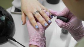 Haga una manicura Una manicura hermosa inusual en un salón de belleza Las muchachas pintan sus clavos Manicura y pedicure almacen de video