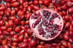 Hagebuttenbeeren und halber Granatapfel Stockfotos