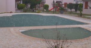 Hagel in een de zomeronweer De ijsballen raken zwaar het zwembad stock videobeelden