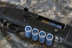 Hagelgevär på kamouflerad bakgrund Royaltyfri Foto