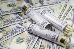 Hagelgevärskal laddade med hundra oss dollarsedlar på olik bakgrund för USA-dollarräkningar Arkivfoto