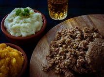 Haggis med mosade potatisar, den mosade svensken och en mycket liten sup av skotsk whisky Brännskadanatt, Skottland arkivbild
