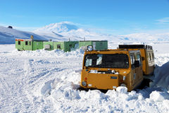 Hagglunds stuck in the snow. Tracked vehicle stuck in the snow at Scott Base, Antarctica with Mount Erebus (an active volcano) in the distance royalty free stock images