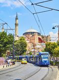 The Hagia Sophia mosque at daylight. Istanbul, Turkey. Istanbul, Turkey - July 10, 2018. A tram and a taxi crossing Divan Yolu street with Hagia Sophia Mosque royalty free stock photos