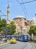 The Hagia Sophia mosque at daylight. Istanbul, Turkey. Istanbul, Turkey - July 10, 2018. A tram and a taxi crossing Divan Yolu street with Hagia Sophia Mosque royalty free stock photography