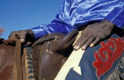 HaHands of an old aboriginal stockman in outbacl Australia. Close up of the hands and fancy outfit of an aboriginal stockman sitting in the saddle Stock Photo