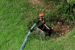 Hahn-Wasser vom Hahnwasserventil, Schieber im grünen Garten lizenzfreie stockbilder