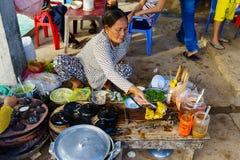 Hai longo, Vietname - 29 de dezembro de 2014: O fast food vietnamiano Banh Xeo e Banh pode vendedores no mercado de peixes longo  Imagens de Stock