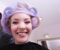 由haidresser的快乐的滑稽的白肤金发的女孩卷发夹路辗在美容院 免版税库存照片