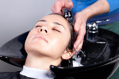 Haidresser washing woman's hair Stock Photography