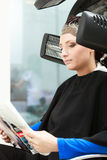 Haidressing salon. Woman dying hair reading magazine. Modern equipment. Royalty Free Stock Photo