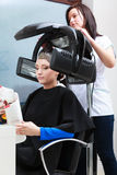 Haidressing salon. Woman dying hair reading magazine. Modern equipment. Stock Photo