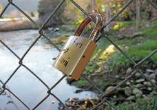 Haie d'engagement avec des serrures le long de rivière Image stock