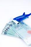 Haifischspielzeug und -geld Stockfotos