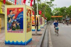 Haifong, Vietnam - 30 de abril de 2015: Un hombre completa un ciclo en la calle que pasa propaganda del día de la reunificación E Fotos de archivo